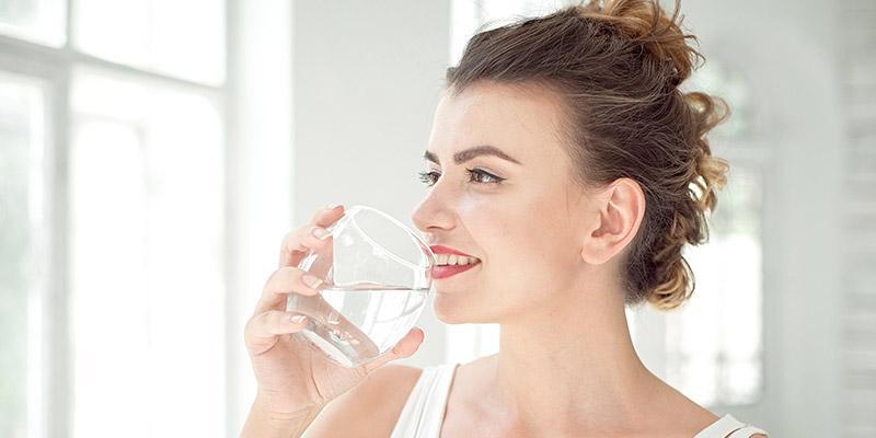 ragazza che beve acqua pulita dal bicchiere