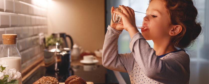 bambina che beve acqua pulita dal rubinetto di casa